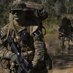 SHOALWATER BAY TRAINING AREA, QUEENSLAND, Australia – Corporal Jesse Wards, a rifleman with the 3rd Marine Expeditionary Brigade's 31st Marine Expeditionary Unit, treks along a road here, June 24, on a unit movement during Exercise Talisman Saber 2007. Talisman Saber is conducted to train an U.S. and Australian joint task force and operations staff in crisis action planning for execution of contingency operations. The exercise involves more than 32,000 personnel from both nations that will focus on improving interoperability and enhancing regional stability.